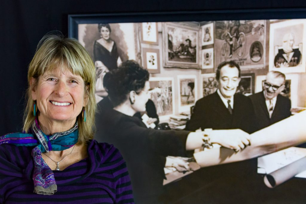 Photo of Lucille Lucas on the left. In the background left to right are: Phyllis Lucas, Salvador Dali, & Sydney Lucas at the first signing of Dali's lithographs in New York, 1964.